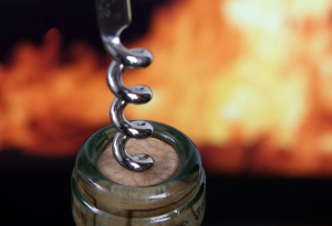 White wine bottle by red fire with corkscrew